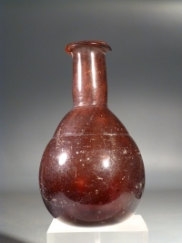 Early Roman amethyst purple glass unguentarium (cosmetic flask).