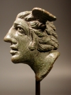 Roman bronze applique winged head of a man with pointed ears.