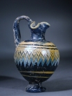 Eastern Mediterranean blue core form glass oinochoe with yellow and turquoise ornament.