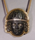 Early Roman bronze applique head of a woman with silver eyes and diadem, set in modern 18k gold setting.